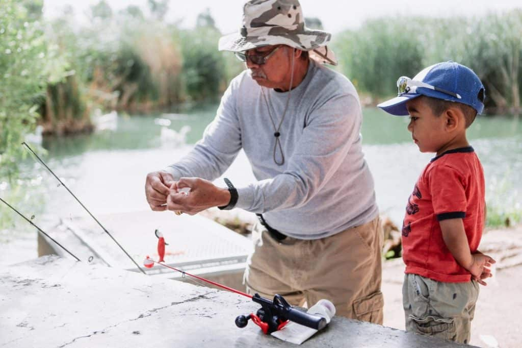 Grand parent teaching grandson to fish at camp site