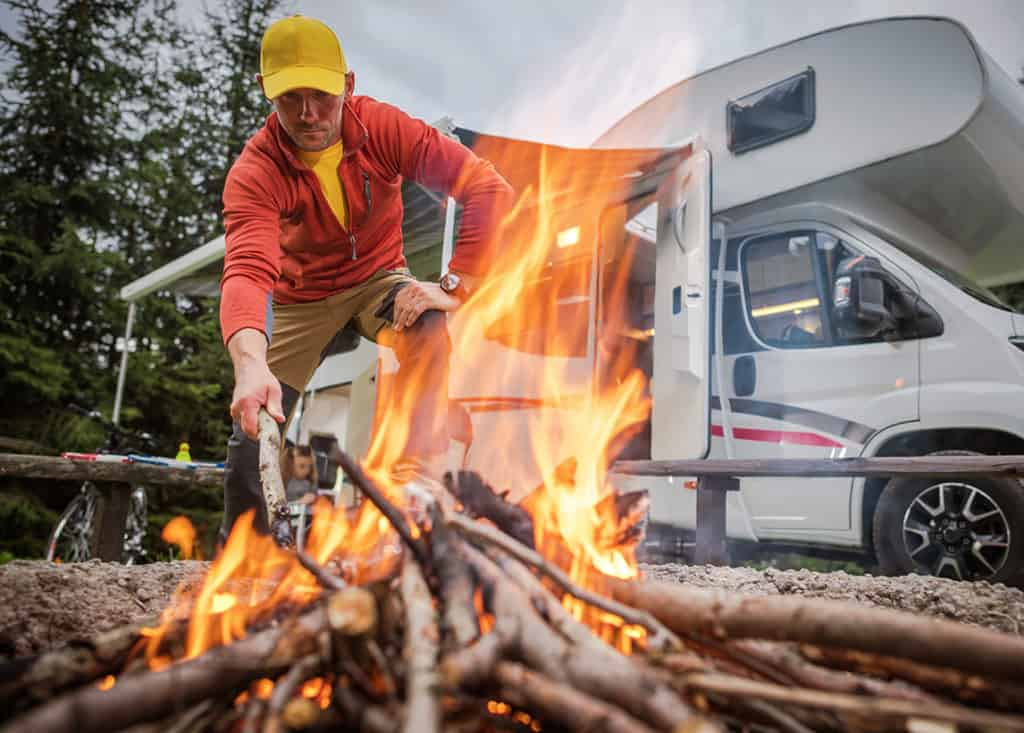 Man enjoying a fire at McGregor's RV Camp